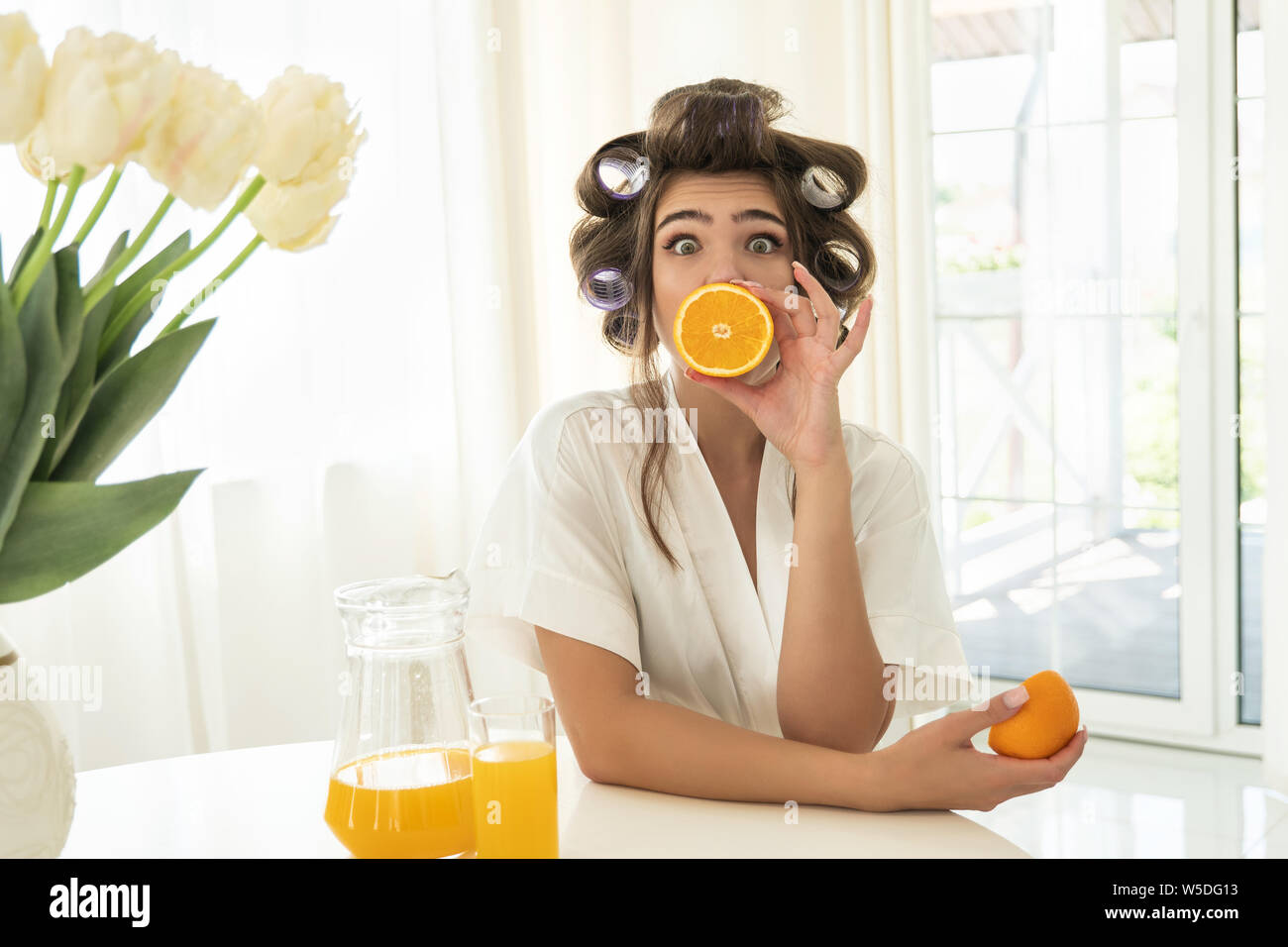 beautiful young surprised brunette woman in hair curlers holding one orange near her mouth and another in her hand in bright kitchen Stock Photo