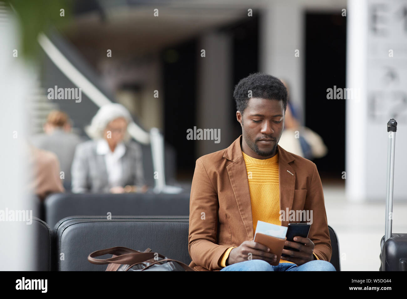 Serious pensive young black man with beard sitting in airport and communicating via online app on phone Stock Photo
