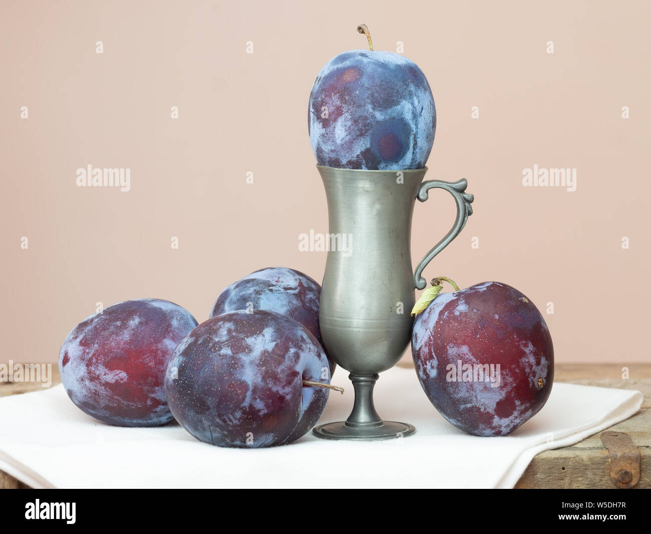 Red plums still life. With serviette, napkin and rustic surface. Stock Photo