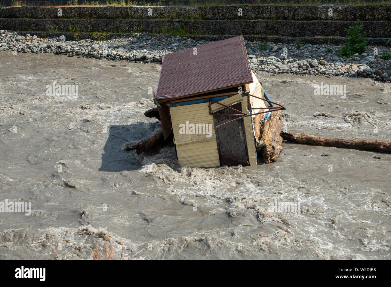 A small house destroyed the mudflow in the mountains. A small house was washed away by a flooded mountain river. The devastating effects of a flood or Stock Photo