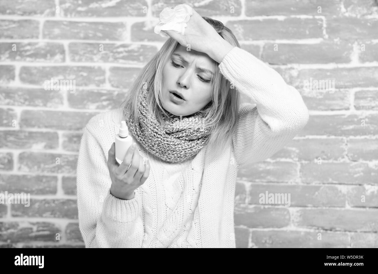 Headache attack. Sick woman injecting drops into nose. Pretty girl with runny nose holding nasal drops. Suffering from asthma or allergic rhinitis. Cute woman nursing nasal cold or allergy. Stock Photo