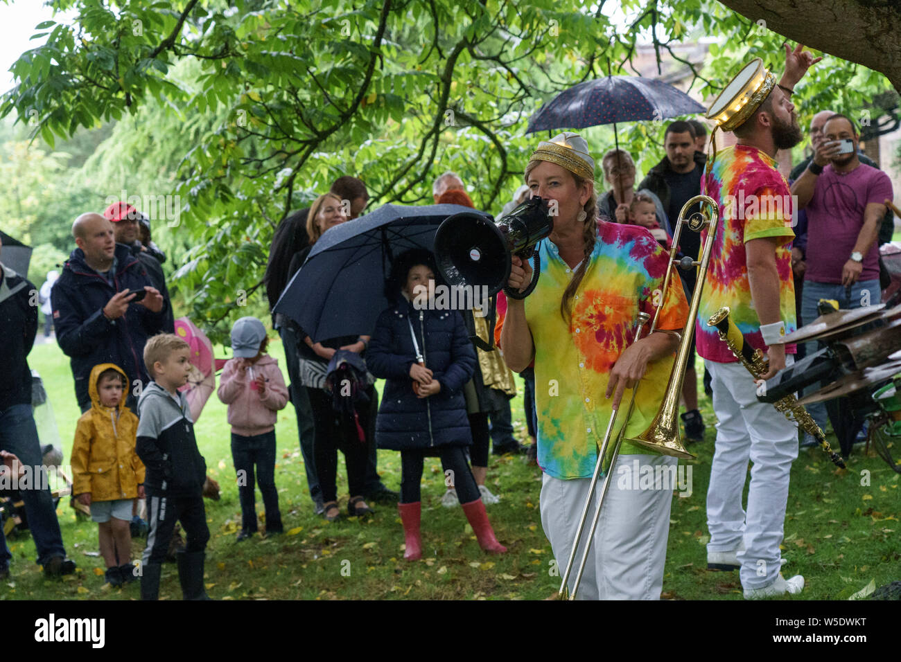 Female Trombone player from Mr Wilson's Second Liners singing through a Loud Hailer at The Valley Gardens Carnival, Harrogate, North Yorkshire, UK. Stock Photo