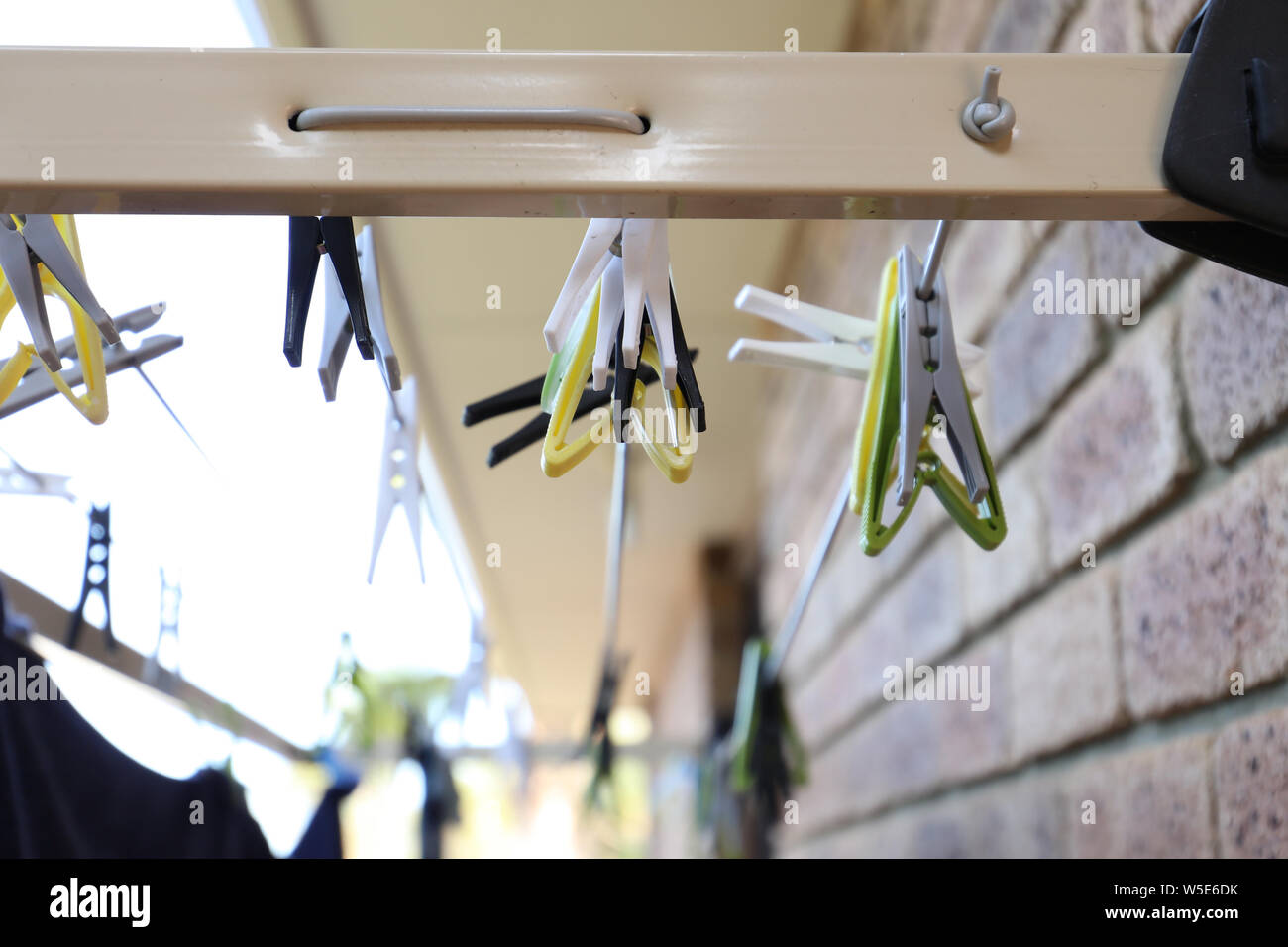 Different coloured washing pegs on an outdoor washing drying line rack attached to the side of the house. Stock Photo