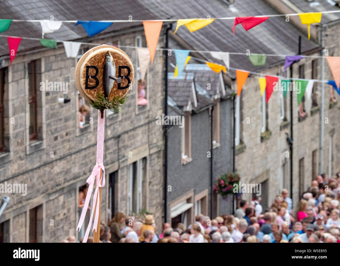 Langholm, Dumfries and Galloway, Scotland, UK. 26th July 2019. The Barley Bannock is held aloft during the walk up the Kirk Wynd. Stock Photo