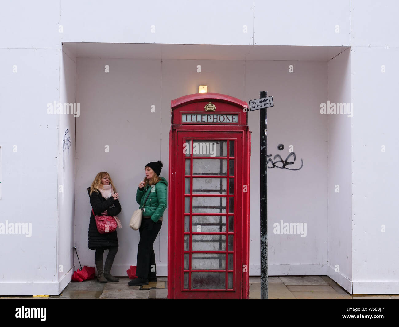 Two people take shelter from the rain next to a classic telephone box and cultural British icon, in London. Stock Photo