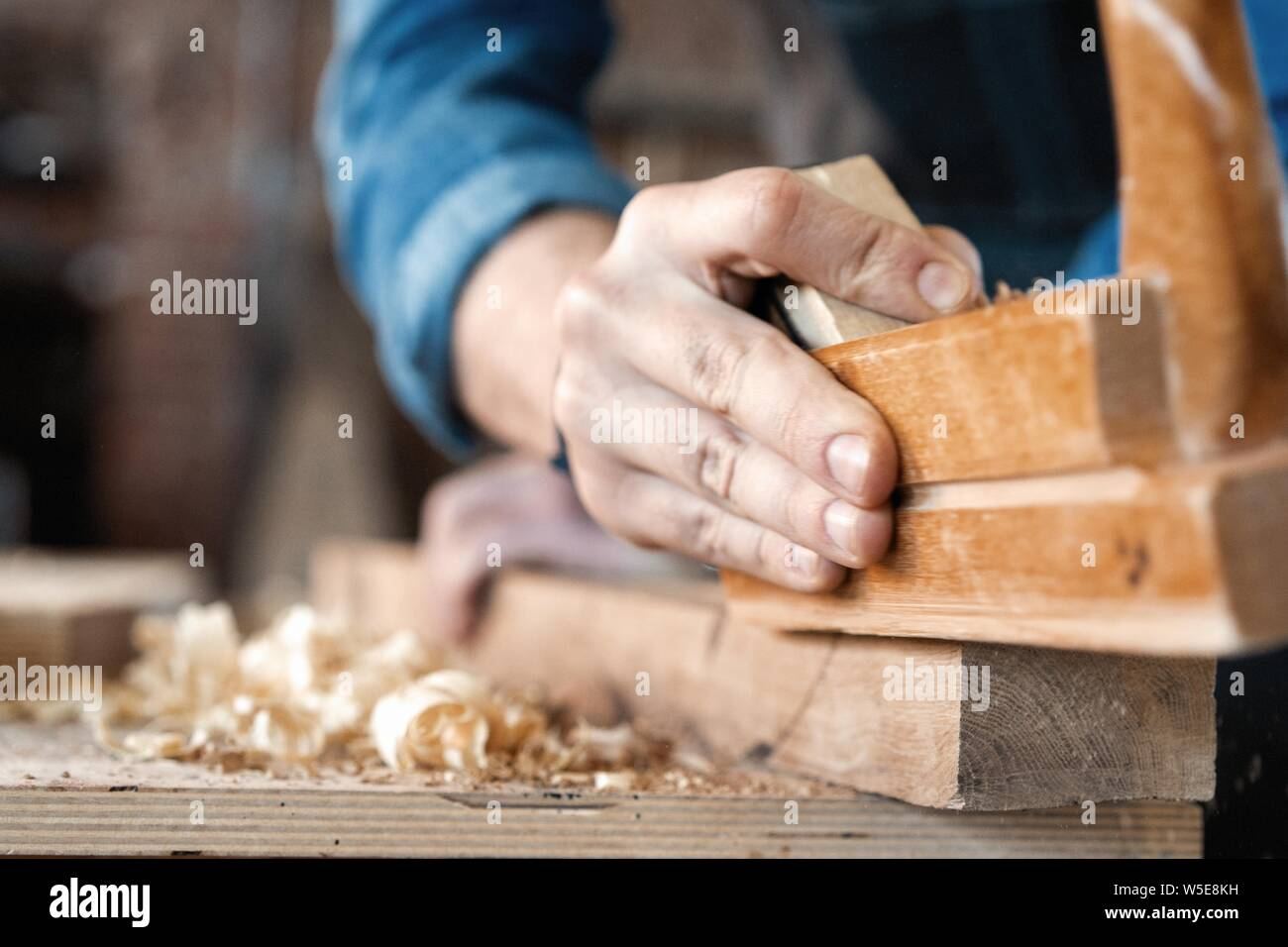 carpenter working with plane on wooden background. Stock Photo