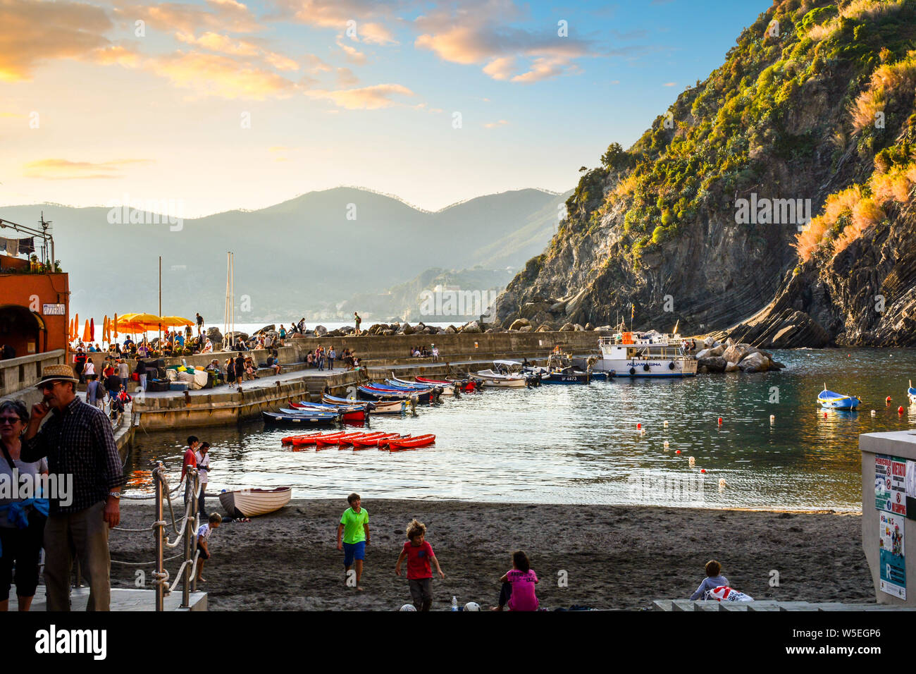 Children play along the sandy beach of Vernazza Italy harbor on the Cinque Terre as tourists enjoy a sunset dinner along the pier. Stock Photo