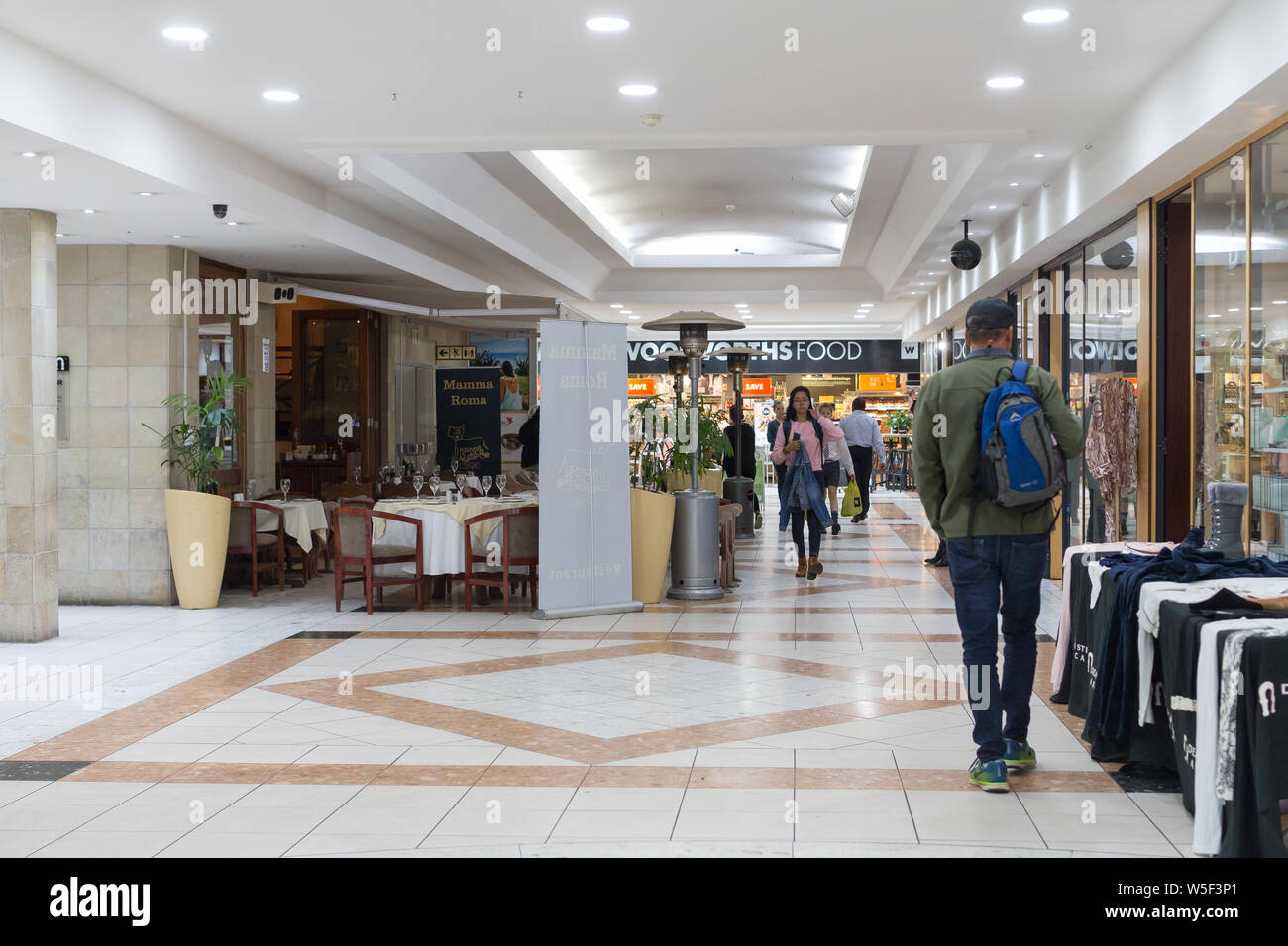 interior of a small shopping centre or mall in Cape Town, South Africa with people or shoppers walking around the shops in Winter Stock Photo