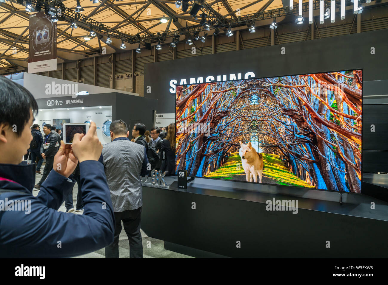 A visitor takes a picture of Samsung's 98-inch 8K QLED TV on
