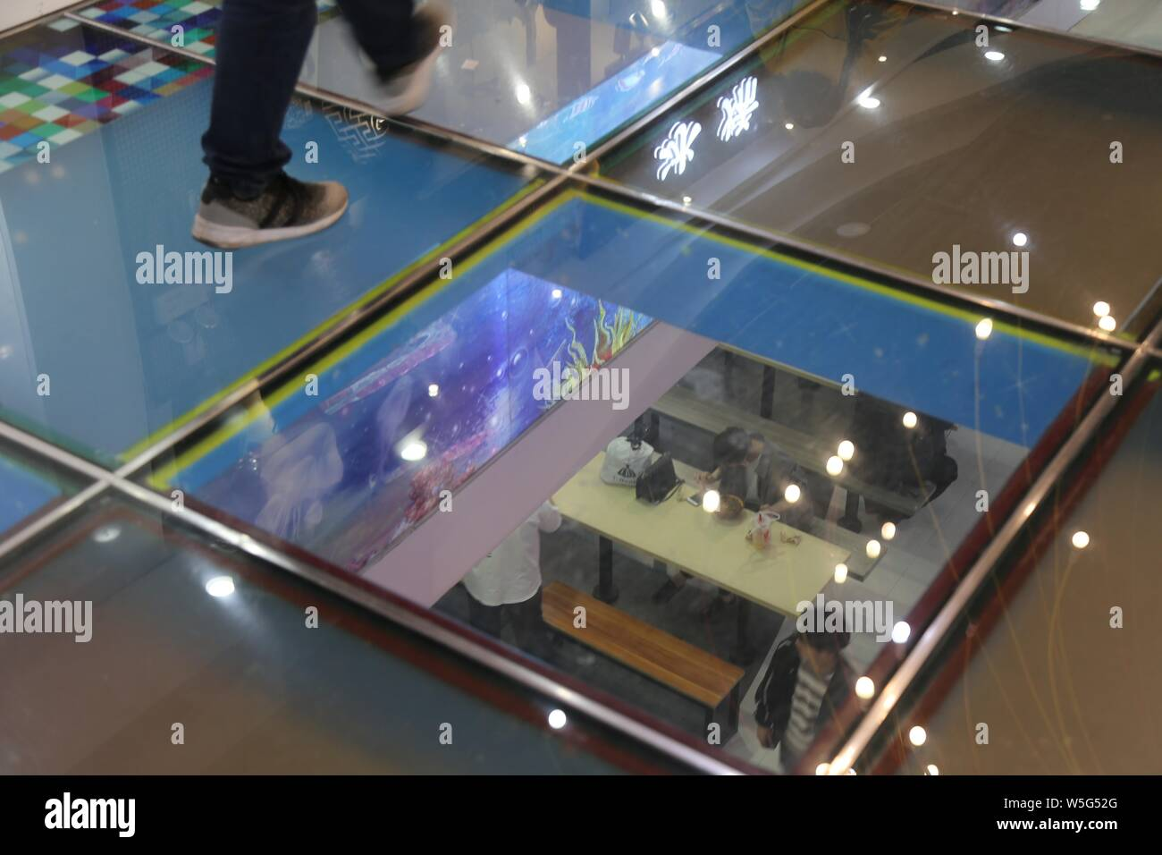 Customers walk on a glass-bottomed walkway at a shopping mall in Zhengzhou city, central China's Henan province, 21 March 2019.    A glass-bottomed wa Stock Photo
