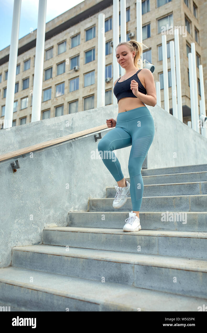 Running in the city sport motivation. Young sporty woman running upstairs on city stairs. Stock Photo
