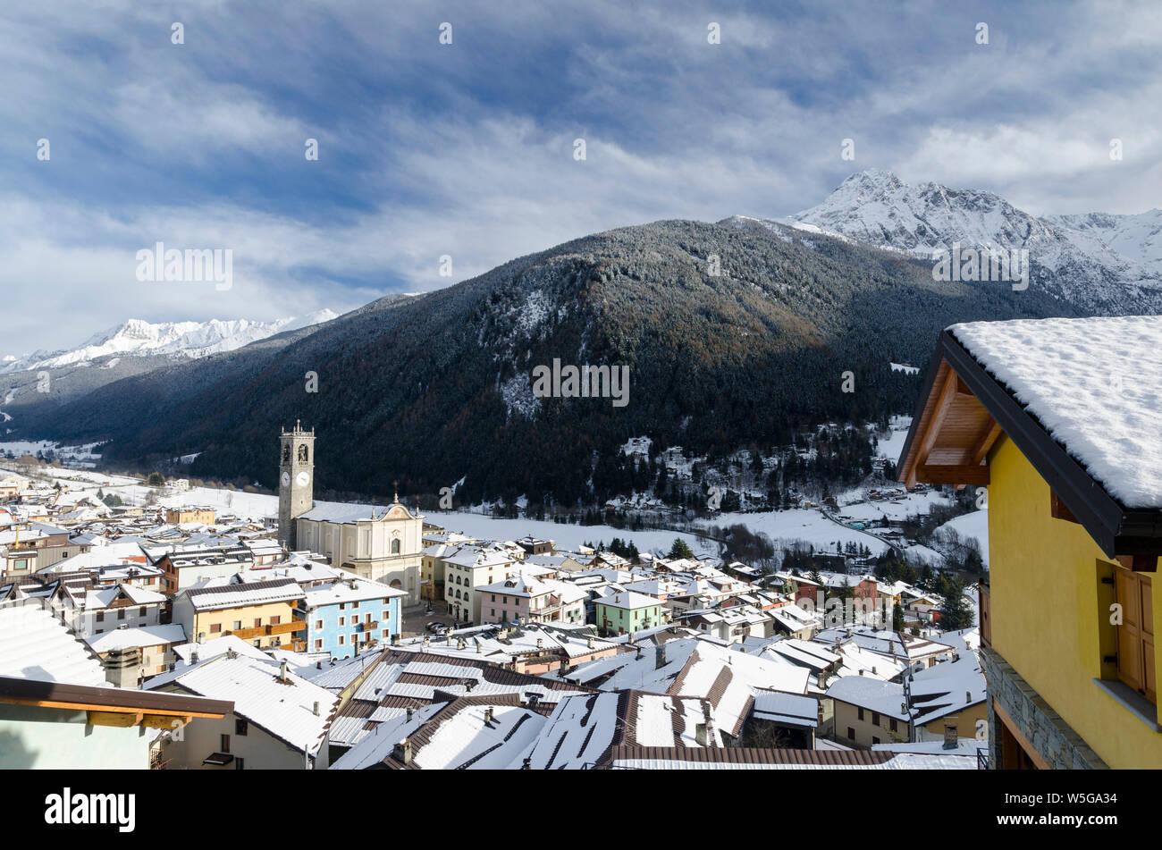Italy, Lombardy, Retiche Alps, Camonica Valley, Adamello Regional Park mountains and Temù-Ponte di Legno ski area from Vezza d'Oglio (fg.: San Martino Parish Church and Mt. Pornina) Stock Photo