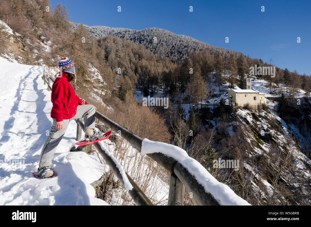 Italy, Lombardy, Retiche Alps, Camonica Valley, snowshoeing along the trail to the ancient alpine church of San Clemente (twelfth century) Stock Photo