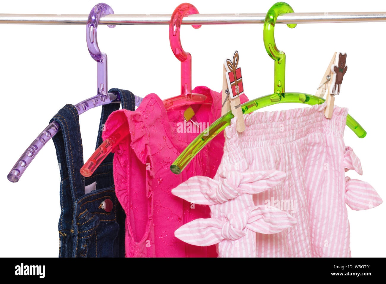 Girls clothes on rack. Close-up of colorful stylish summer dresses and a short pants for the little girl on a rack isolated on a white background. Clo Stock Photo