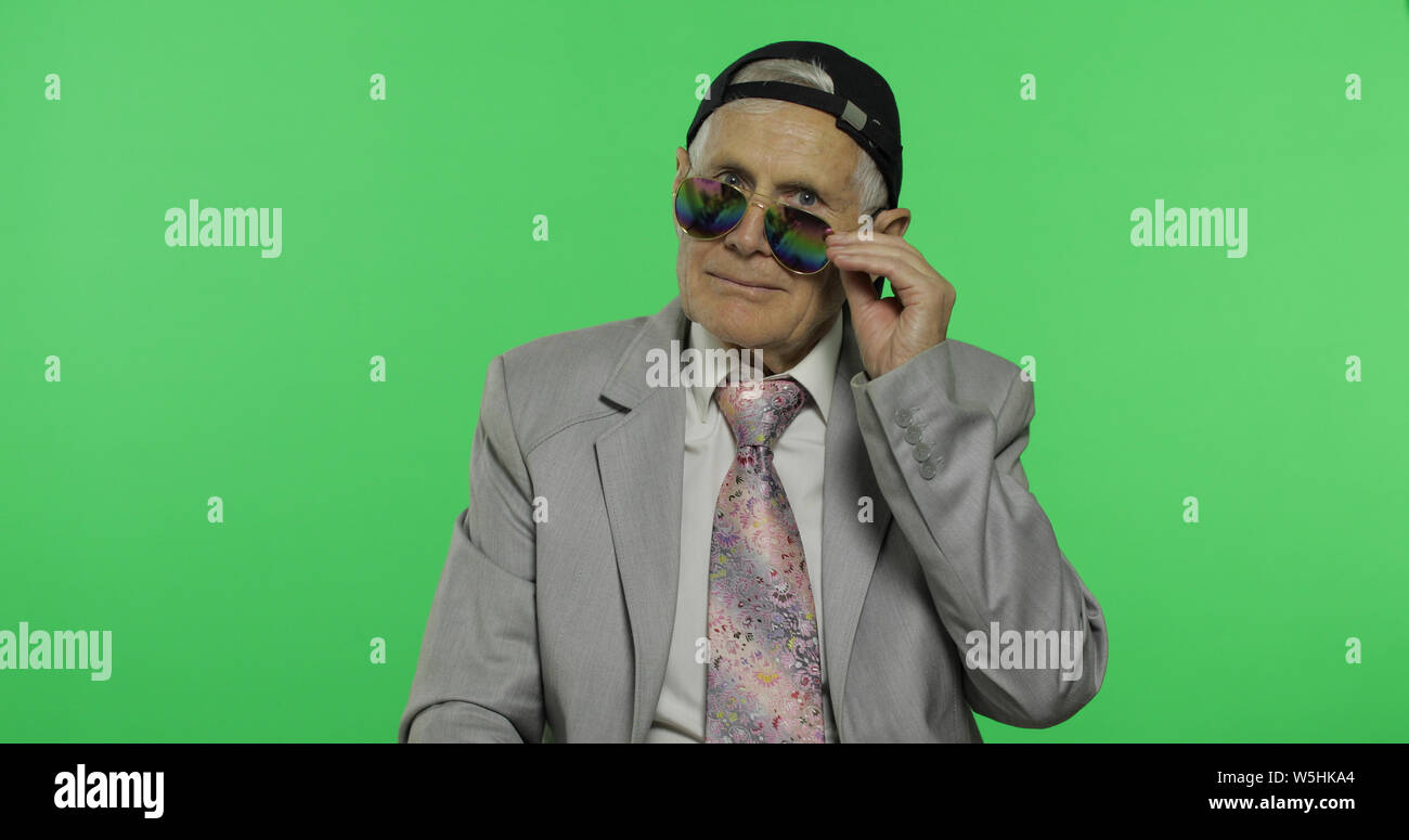 Funny elderly businessman in sunglasses and cap smiles. Old man in formal wear winks on chroma key background. Place for your logo or text. Green screen background Stock Photo
