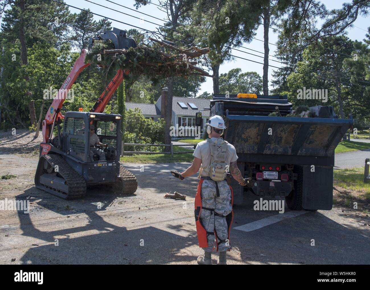 Airmen from the Massachusetts Air National Guard's 102nd Civil Engineer Squadron mobilized to support recovery efforts in the wake of two tornadoes that touched down on Cape Cod on July 23, 2019, July 25, 2019. The Airmen cleared fallen trees and debris from roadways in the towns of Dennis and Harwich Massachusetts. Image courtesy Tech. Sgt. Thomas Swanson/102nd Intelligence Wing. () Stock Photo