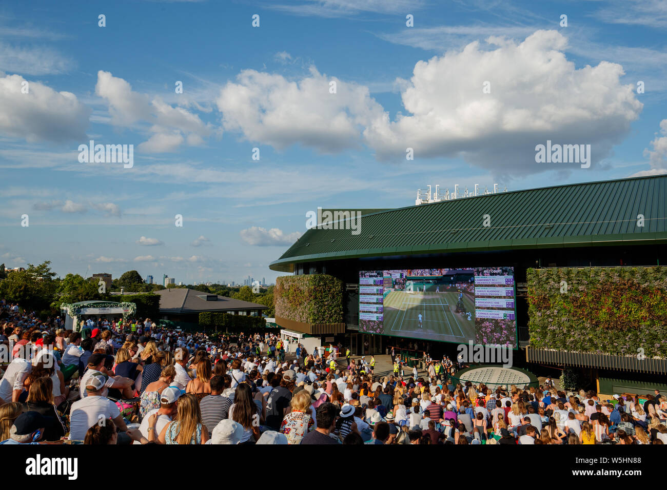 Fans and spectators on Henman Hill , Murray Mound or Aorangi Hill with the big screen on No.1 Court during The Championships at Wimbledon 2019. Stock Photo