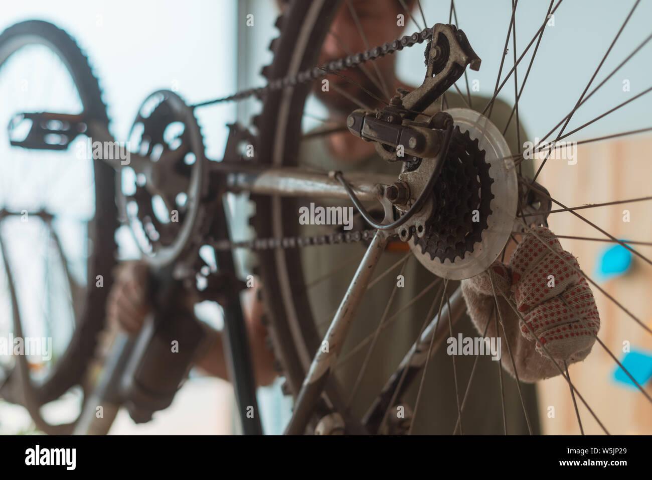 Man repairing old hardtail mountain bike in workshop, selective focus Stock Photo