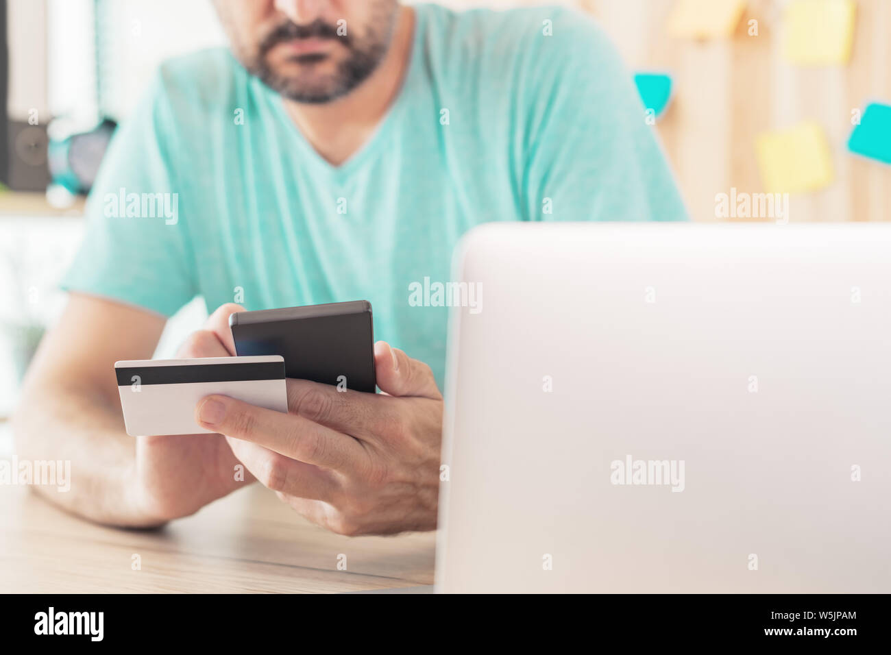 Online shopping with credit card and smart phone, casual man