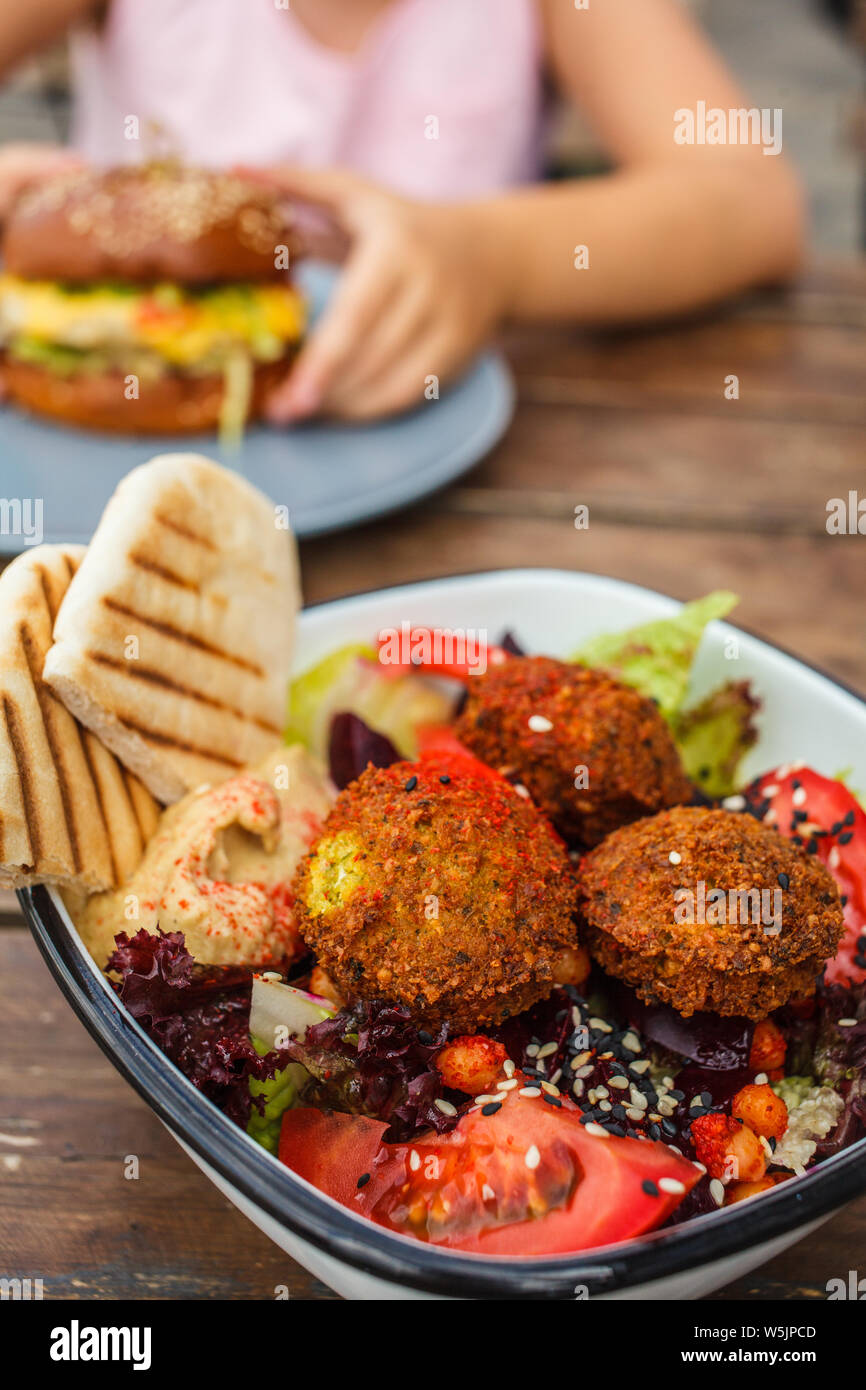 Israeli street food. Falafel salad with hummus, beetroot and vegetables in a bowl in a restaurant. Stock Photo