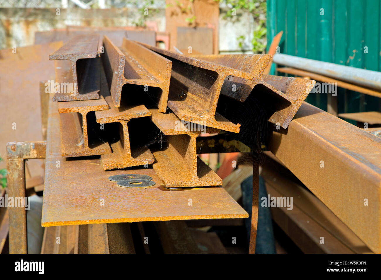 A heap of rusted iron girders or rolled steel joists left outside in a yard Stock Photo