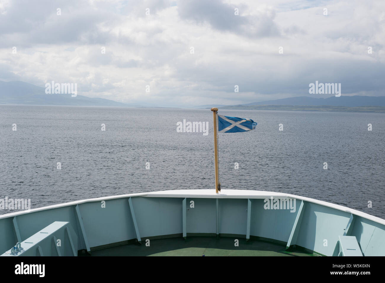 Scottish flag on the bow of a Caledonian Macbrayne ferry leaving the port in Oban, Scotland, travelling towards the Isle of Islay. Stock Photo