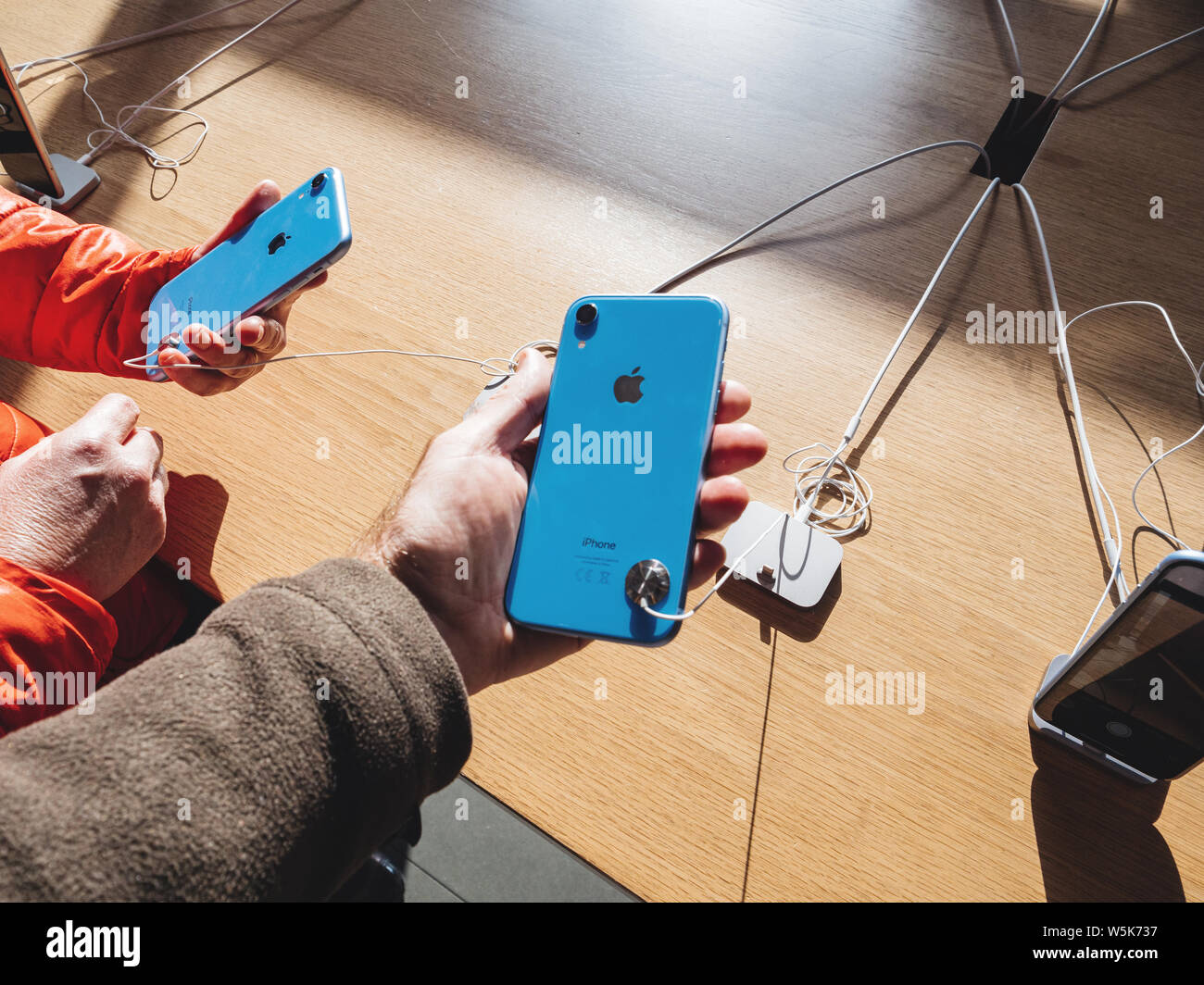 Paris, France - Oct 26, 2018: Man and woman hand holding two latest blue with silver logotype iPhone XR smartphone during launch day manufactured by Apple Computers Stock Photo