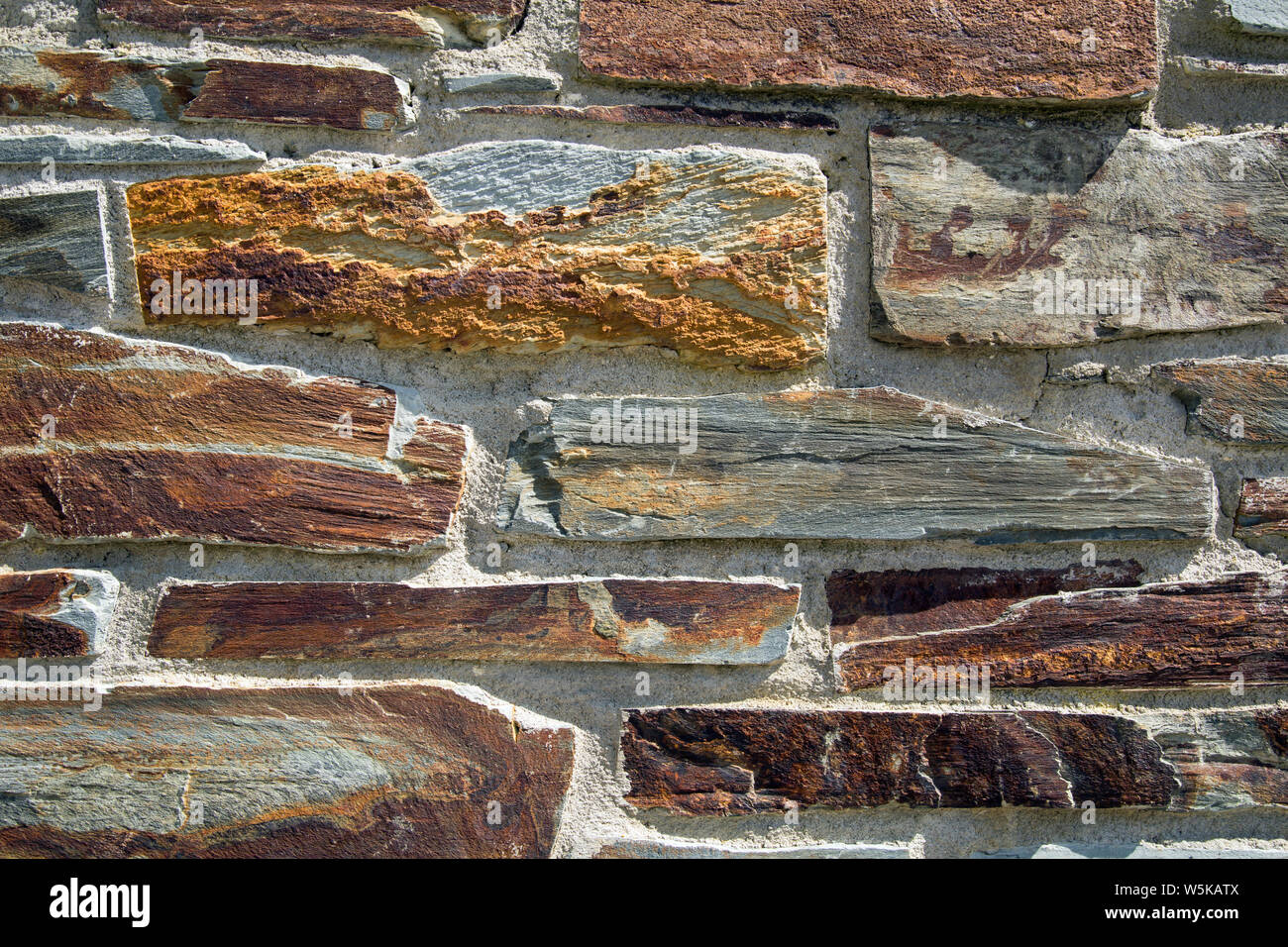 Rust coloured stone brick wall shot close up for a