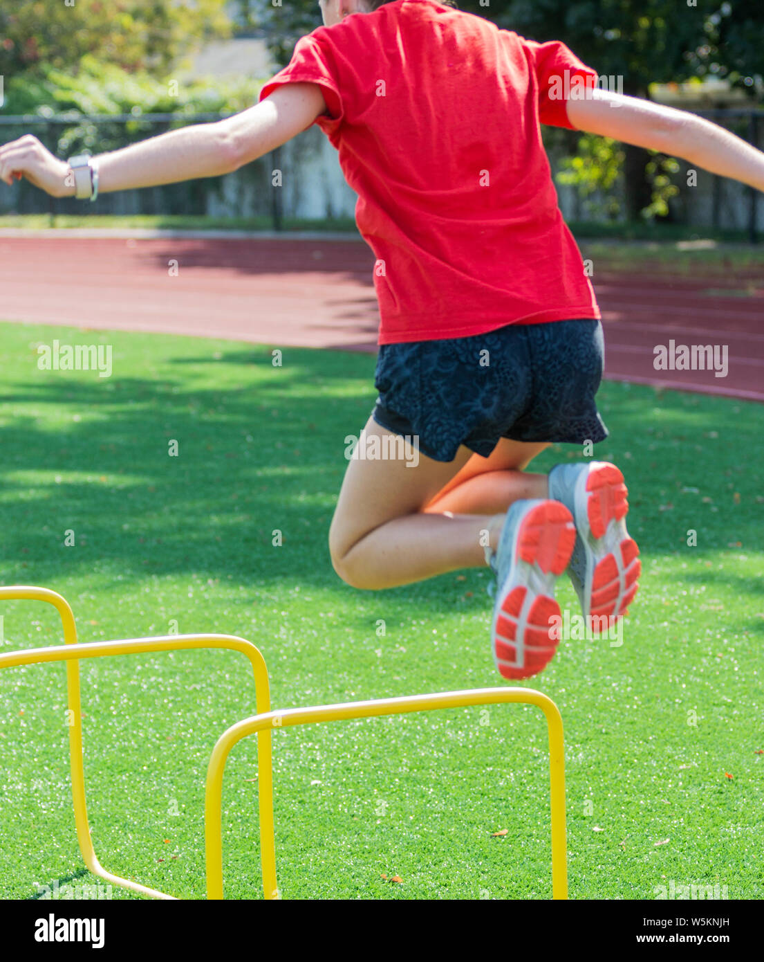 A high school teenage girl is jumping over two foot high yellow mini hurdles during track and field practice on a green turf field. Stock Photo