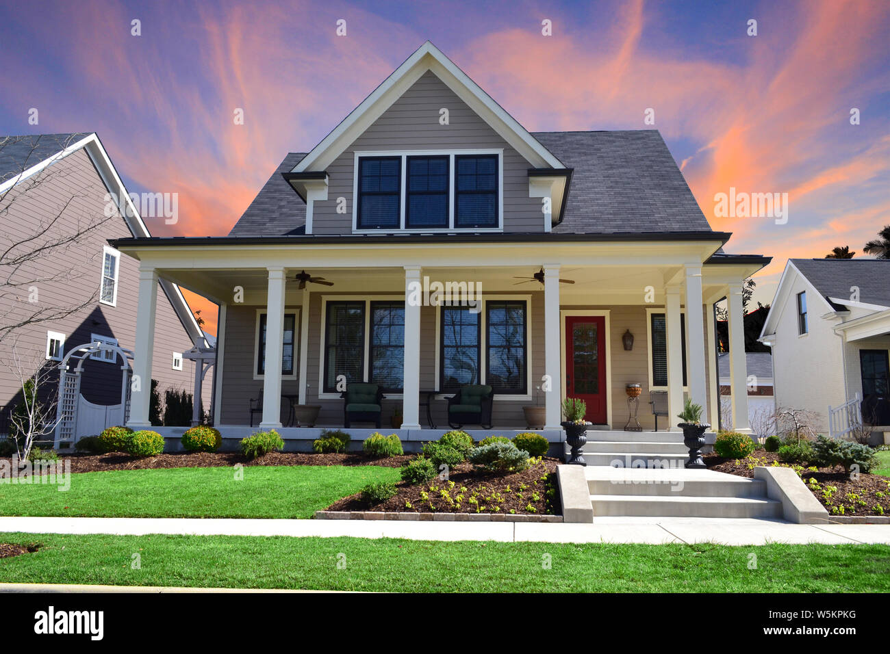 Sunset Behind A Single Family Suburban Craftsman House With Big Front Porch White Pillars And A Red Front Door Stock Photo Alamy