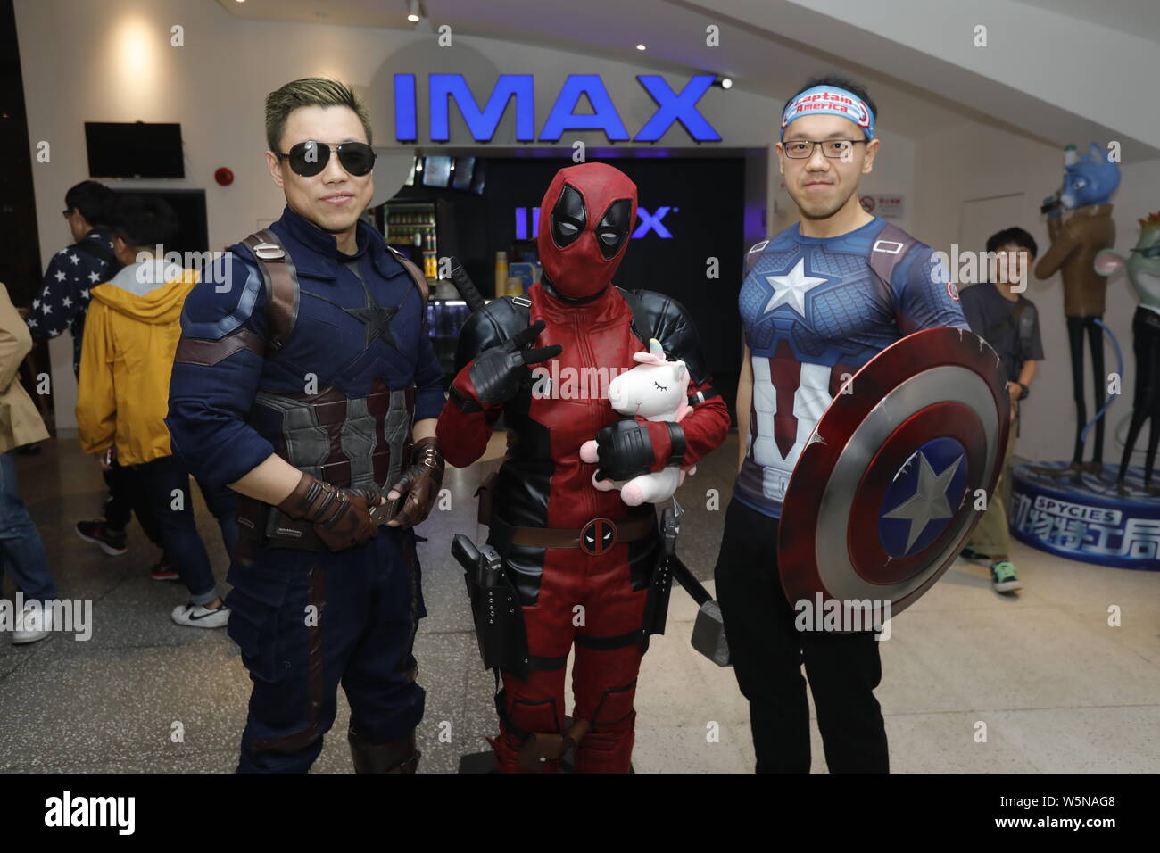 """Chinese filmgoers wearing costumes of Avengers superheroes wait inside a cinema before the midnight premiere of Disney and Marvel's """"Avengers: Endgame Stock Photo"""