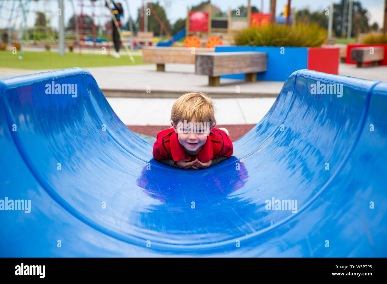 A two-year old boy goes down a blue slide on his tummy, having fun at a new playground, in Canterbury, New Zealand Stock Photo