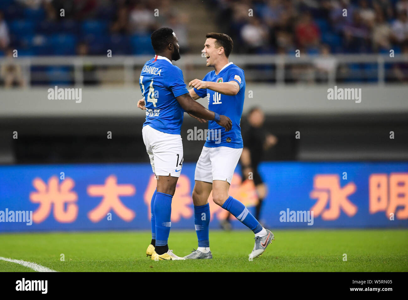 Cameroonian football player Franck Ohandza, left, of Henan Jianye celebrates with English-born Taiwanese football player Tim Chow after scoring agains Stock Photo
