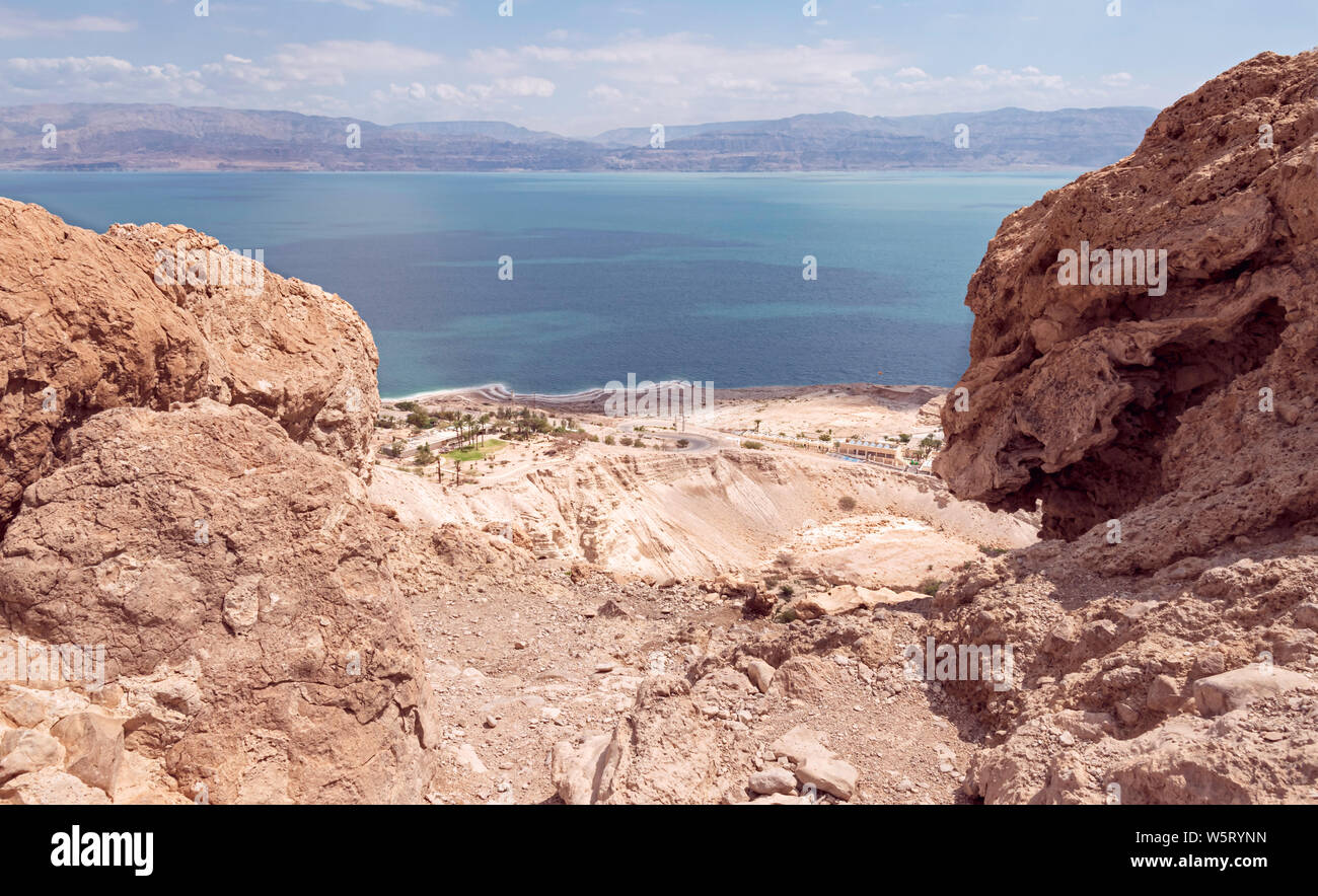 the dead sea and ein gedi field school from above near david falls with the Jordan Moav mountains in the background and a grinning boulder in the fore Stock Photo
