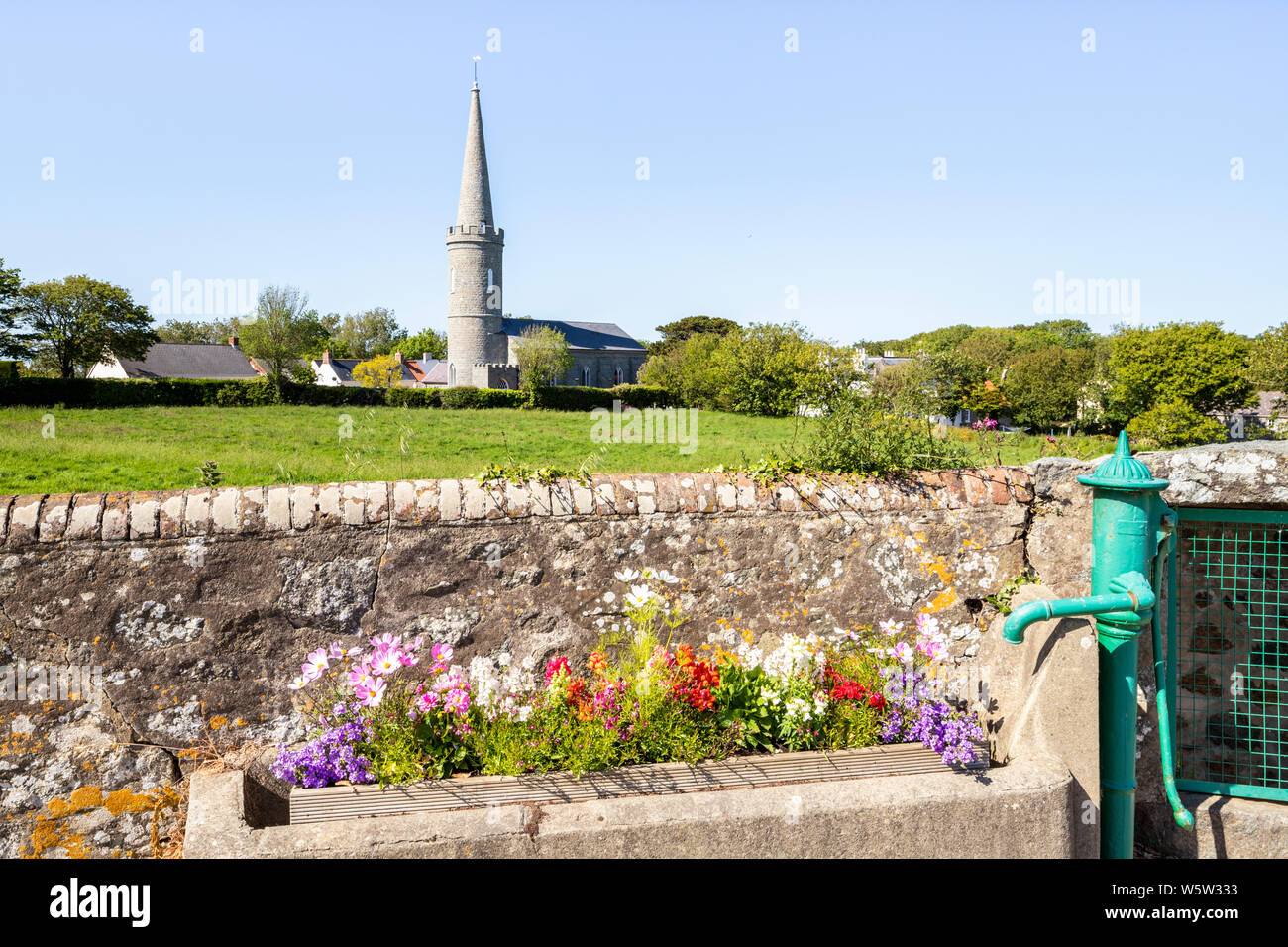 Flowers in an old water trough next to a pump in Torteval, Guernsey, Channel Islands UK Stock Photo