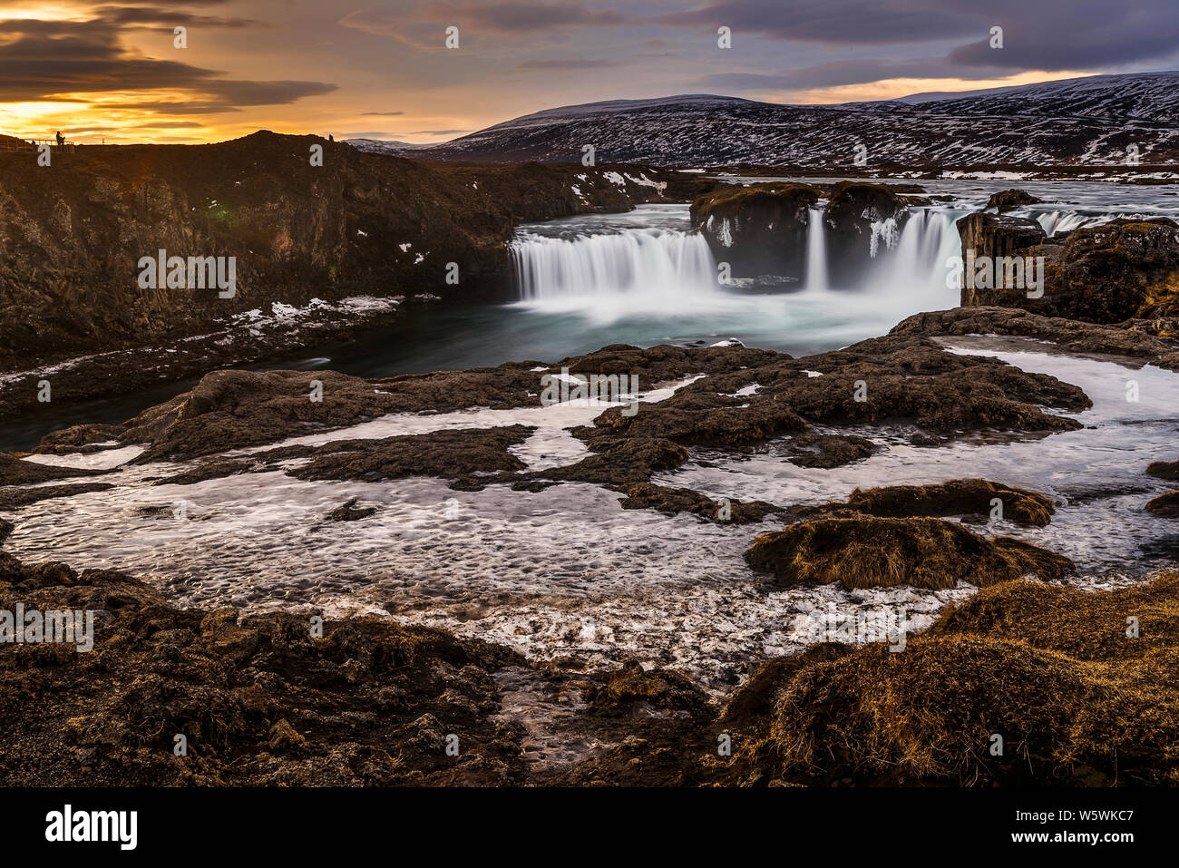 Melted glacier water flowing in frozen godafoss waterfalls at sunrise, Iceland Stock Photo