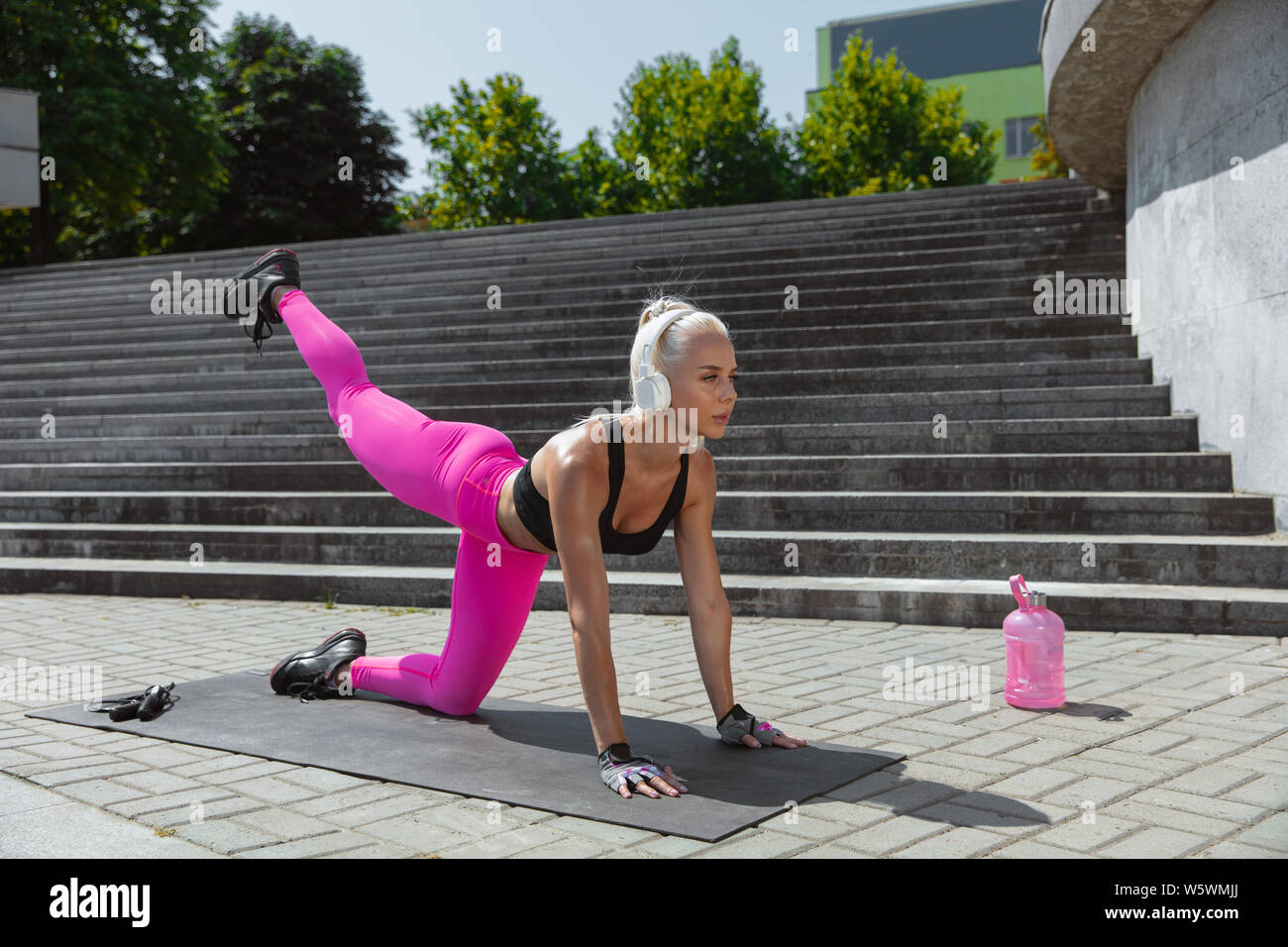 A Young Athletic Woman In White Headphones Training Listening To The Music At The Street Outdoors Working Lower Body Out On Mat Concept Of Healthy Lifestyle Open Air Sport Activity Weight Loss Stock