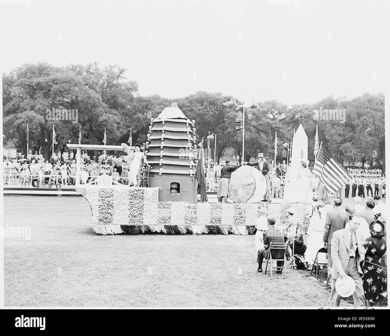 President Truman attends ceremonies celebrating the 100th anniversary of the Washington Monoument. He watches the parade from the reviewing stand. Stock Photo