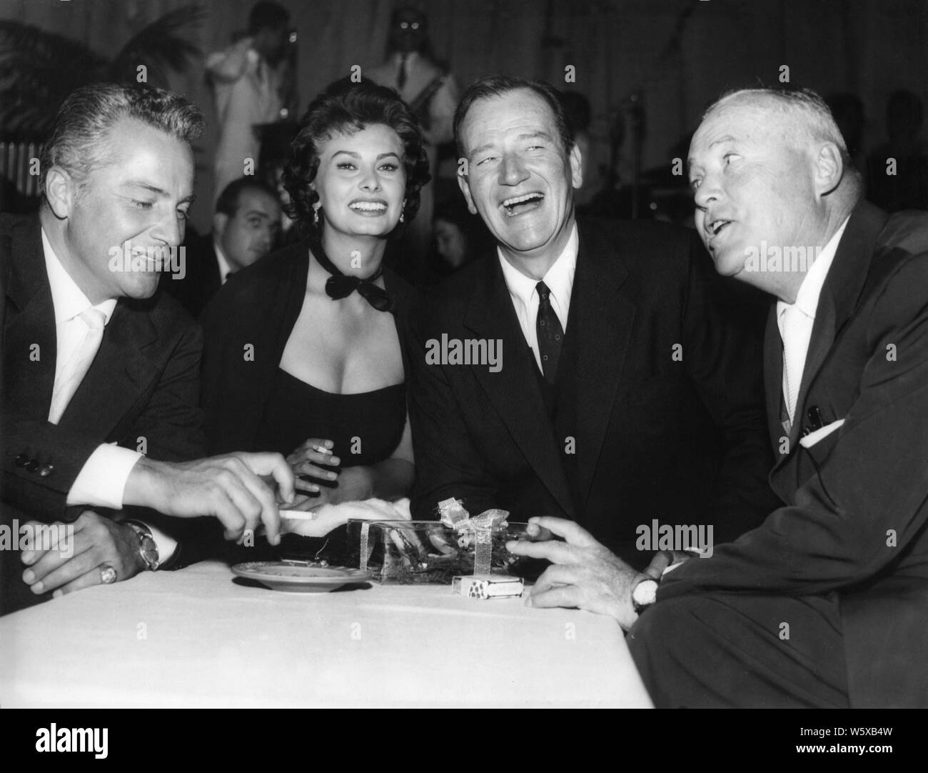 ROSSANO BRAZZI SOPHIA LOREN JOHN WAYNE and director HENRY HATHAWAY candid during filming LEGEND OF THE LOST 1957 Batjac Productions / Dear Films Produzione / United Artists Stock Photo
