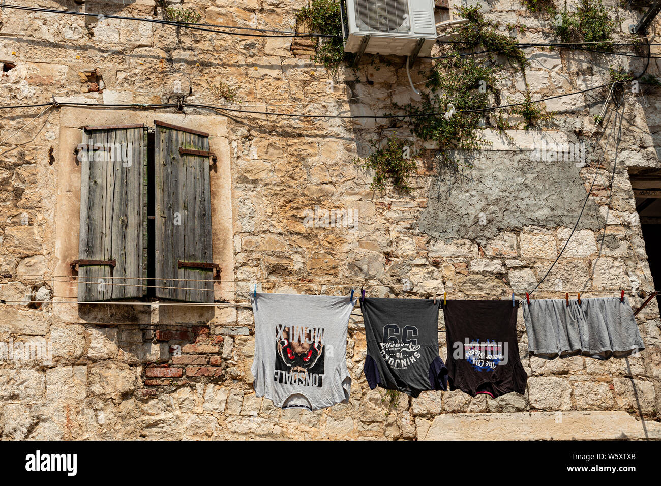 Shuttered window and clothes in a Split backstreet, Croatia Stock Photo