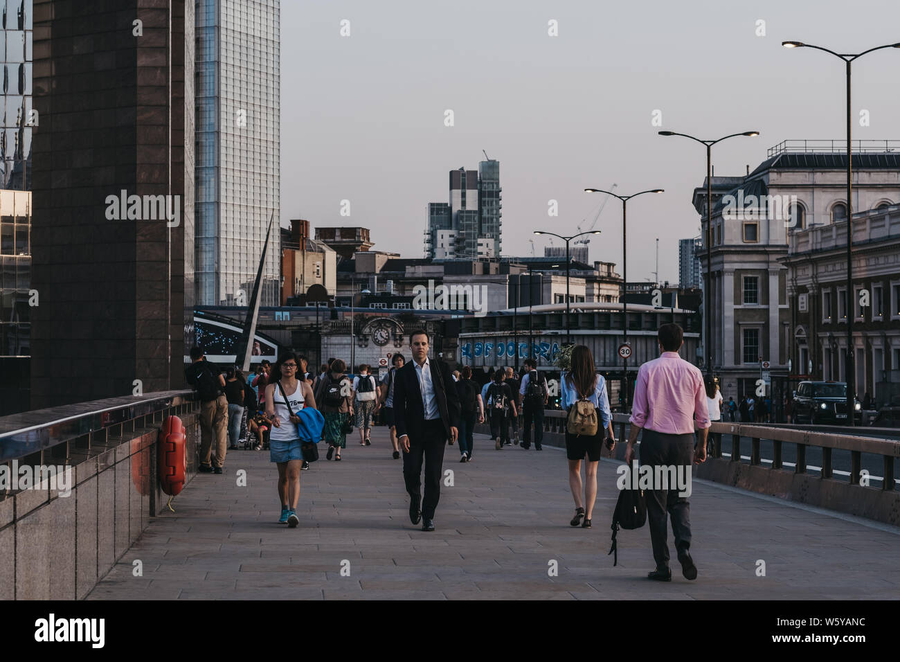 London, UK - July 23, 2019: People walking on London Bridge during blue hour, selective focus, city on the background. London is one of the most visit Stock Photo