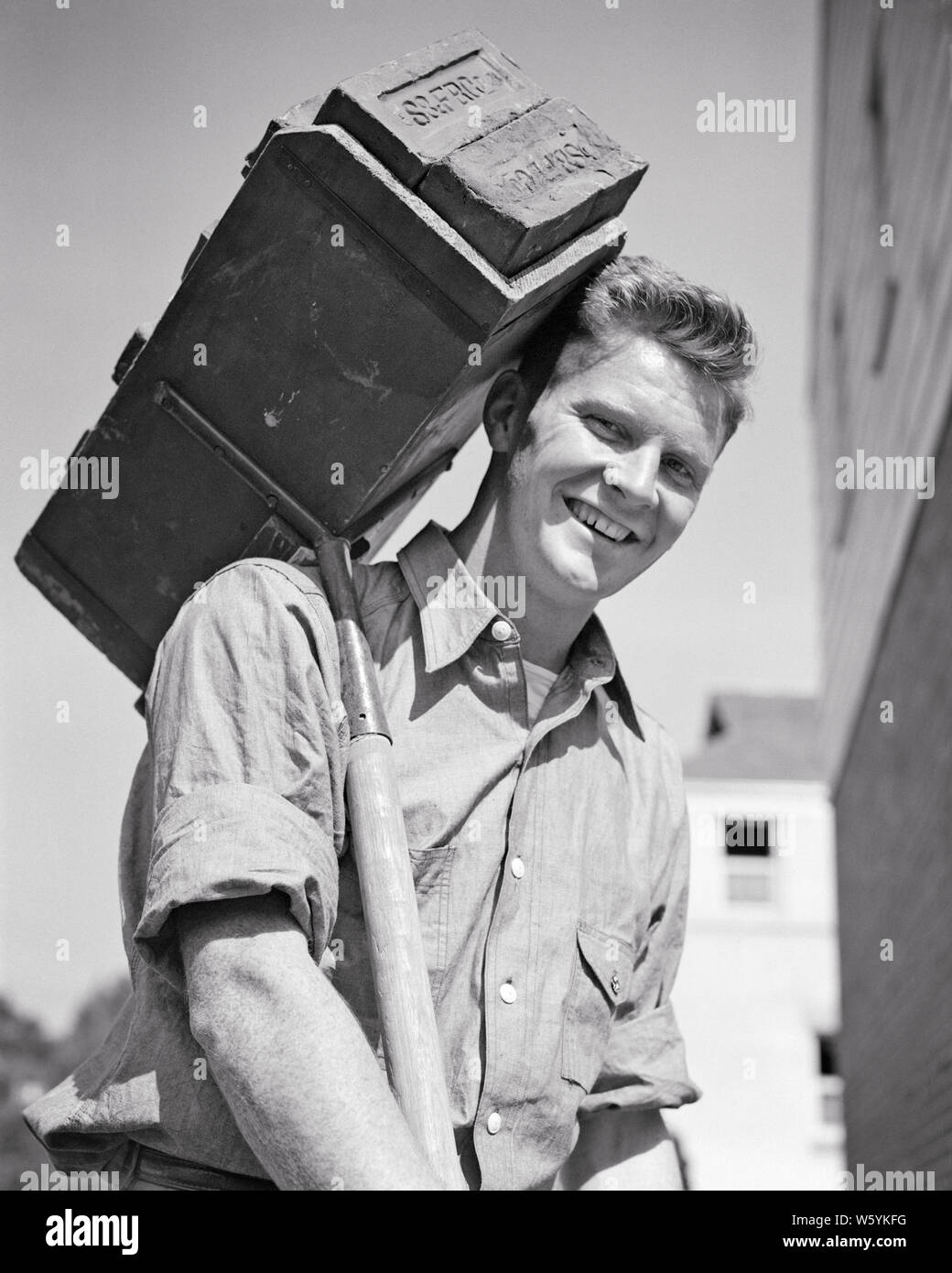 1940s SMILING MAN CONSTRUCTION WORKMAN MASON LOOKING AT CAMERA AT HOUSE BUILDING SITE CARRYING A HOD FULL OF BRICKS - b18748 HAR001 HARS 1 FITNESS FACIAL MORTAR CAREER HEALTHY YOUNG ADULT BALANCE SAFETY STRONG WORKMAN PLEASED JOY LIFESTYLE HOUSES JOBS SITE BRICKS HALF-LENGTH PHYSICAL FITNESS PERSONS RESIDENTIAL MALES RISK BUILDINGS PROFESSION CONFIDENCE EXPRESSIONS B&W EYE CONTACT SKILL ACTIVITY MATERIAL OCCUPATION HAPPINESS PHYSICAL SKILLS CHEERFUL STRENGTH CAREERS LOW ANGLE PRIDE MASON A AT OF HOMES OCCUPATIONS SMILES CONCEPTUAL FLEXIBILITY JOYFUL MUSCLES RESIDENCE OR MID-ADULT MID-ADULT MAN Stock Photo