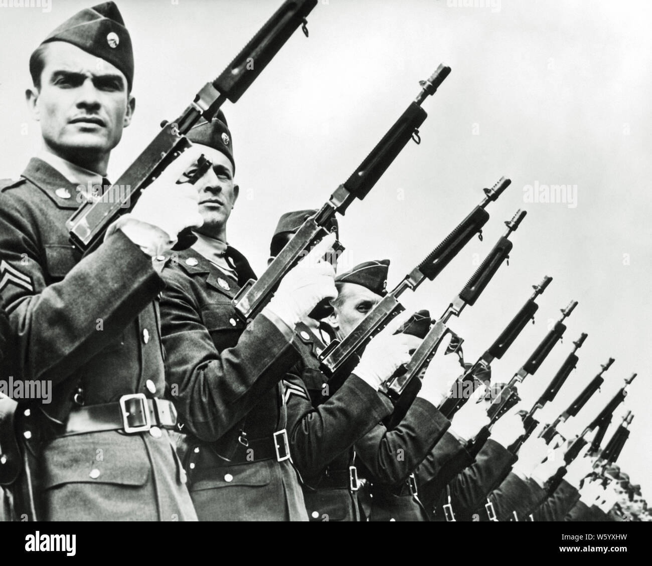 1930s 1940s FILE OF US ARMY SOLDIERS MILITARY POLICE WEARING WHITE GLOVES HOLDING THOMPSON 45 CALIBER SUBMACHINE GUNS AT READY - q74001 CPC001 HARS RISK CONFIDENCE EXPRESSIONS B&W EYE CONTACT FREEDOM FILE PROTECTION STRENGTH COURAGE POWERFUL STERN WORLD WARS WORLD WAR WORLD WAR TWO WORLD WAR II OF AUTHORITY OCCUPATIONS UNIFORMS CONCEPTUAL STYLISH WORLD WAR 2 US ARMY WHITE GLOVES FIREARM FIREARMS TOGETHERNESS YOUNG ADULT MAN BLACK AND WHITE CAUCASIAN ETHNICITY OLD FASHIONED Stock Photo