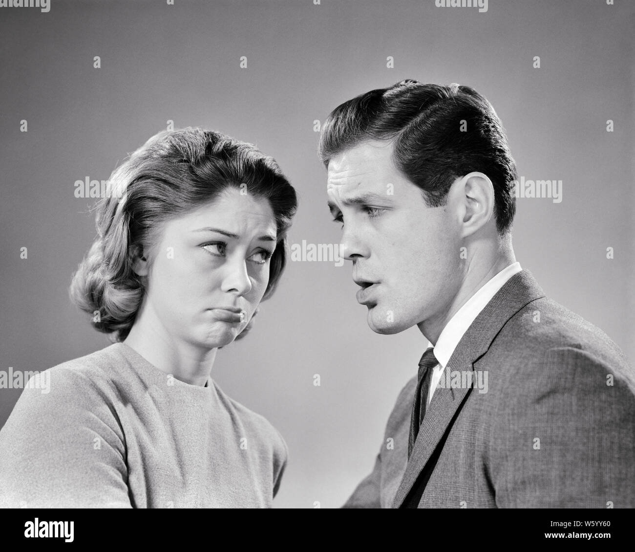 1960s young couple looking at one another with angry mad facial expressions - s13057 HAR001 HARS OLD FASHION 1 FACIAL ANGER COMMUNICATION YOUNG ADULT SAFETY LIFESTYLE ANNOYED FEMALES MARRIED STUDIO SHOT MOODY SPOUSE HUSBANDS HOME LIFE COPY SPACE FRIENDSHIP HALF-LENGTH LADIES MARRIAGE PERSONS CARING MALES EXPRESSIONS TROUBLED B&W PARTNER SADNESS SUIT AND TIE DISAGREEING DISTRESSED POUTING IRATE DISAGREEMENT HURTFUL AT DISAGREE HURT MOOD CONNECTION CONCEPTUAL GLUM SPAT STYLISH DISPLEASURE HOSTILITY NEWLYWED PETULANT ANNOYANCE ANOTHER EMOTION EMOTIONAL IRRITATED MISERABLE QUARREL SQUABBLE WIVES Stock Photo