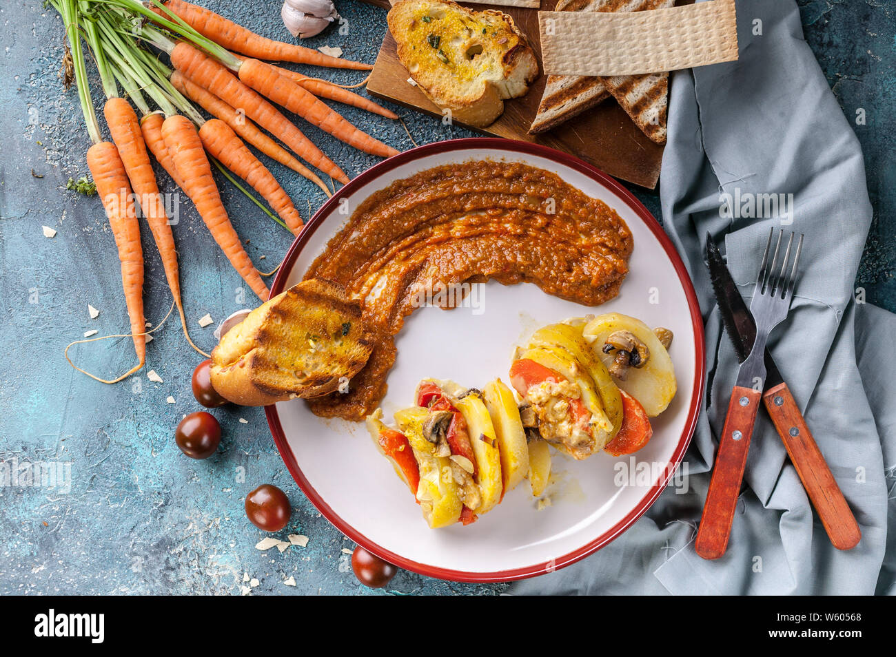 Vegetarian food. Stewed potatoes with zucchini, carrots, mushrooms and cheese. Carrot mash with champignons. Top view Stock Photo