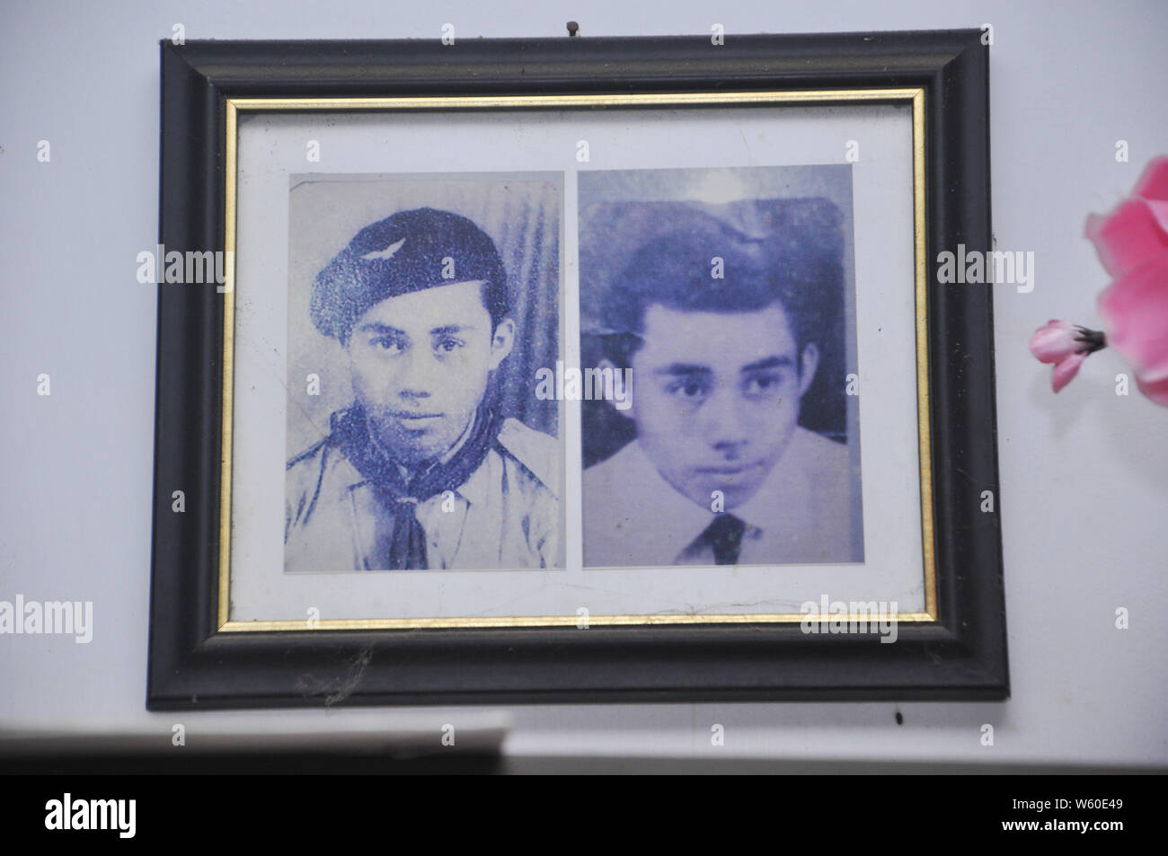 Old photographs of young Andarias Sarra, now 80 years old, hanging on the wall. Mr. Sarra survives from two stroke attacks. He first got stroke in 201 Stock Photo