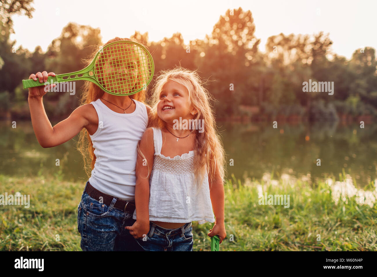 Little girl playing badminton with sister in summer park. Kids having fun outdoors. Close up of shuttlecock and racket Stock Photo