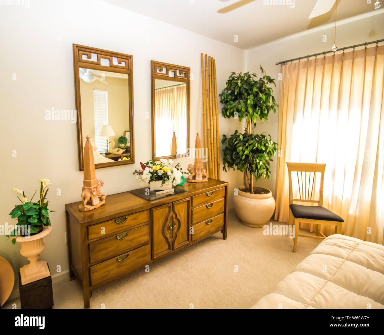 Bedroom With Dresser Mirrors And Bamboo Decorations Stock