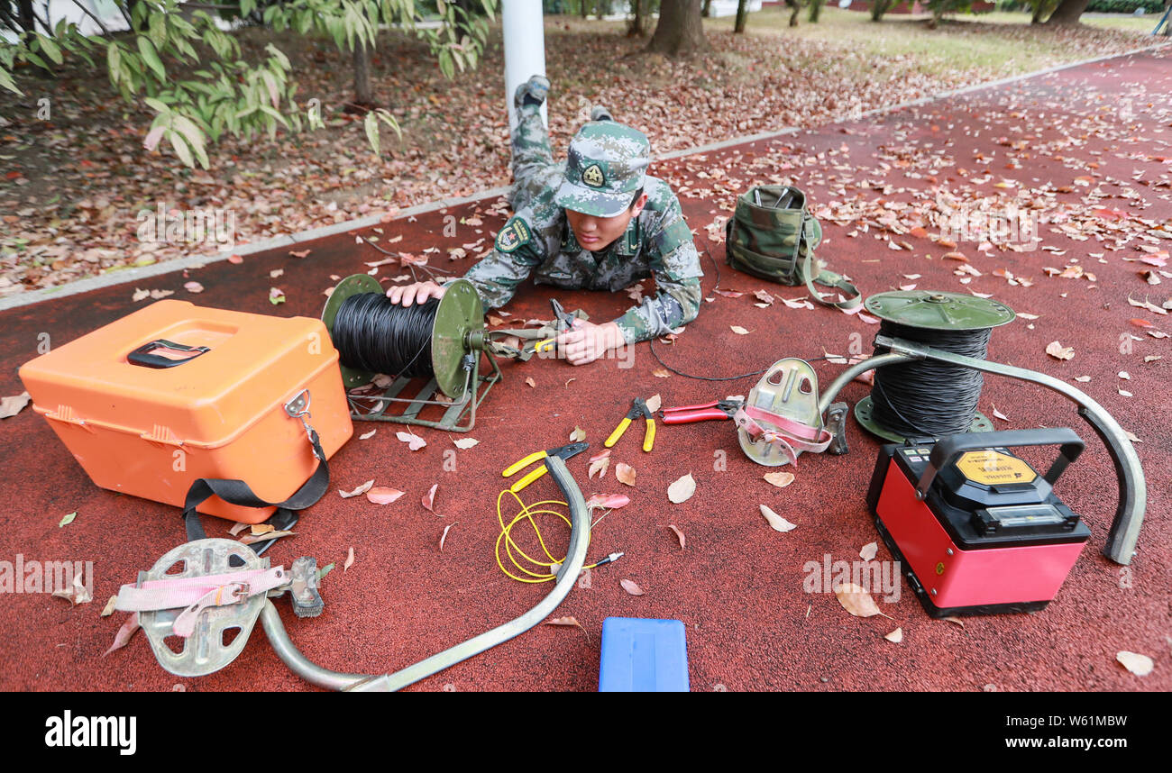 A Chinese PLA (People's Liberation Army) soldier and telecommunication cable inspector lies on the ground close to his equipment as he pretends to hav Stock Photo