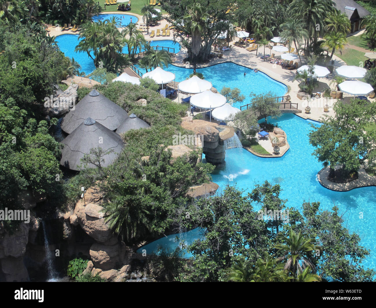 aerial view or looking down on a hotel resort swimming pool surrounded by trees and umbrellas with turquoise blue water at Sun City, South Africa Stock Photo